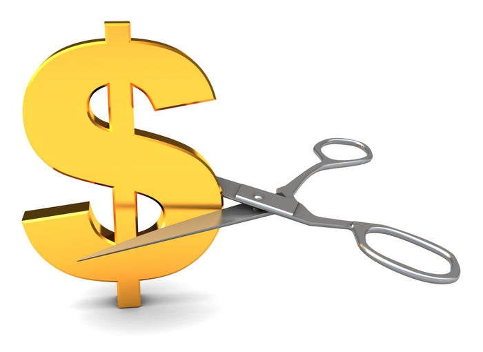 Scissors about to cut a gold dollar sign