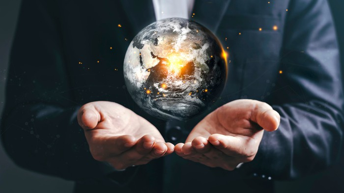 A rendering of Earth in the palms of a businessman's outstretched hands.
