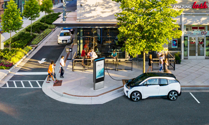 Car plugged into a Volta charging station on a retail shopping plaza, with a large screen showing advertising.
