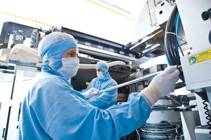 A technician works in a cleanroom with a semiconductor assembly machine.