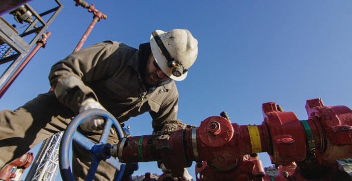 An oil and gas worker next to a pipeline valve.