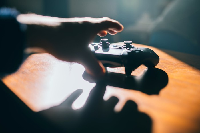 Hand reaching for a video game controller on a table.