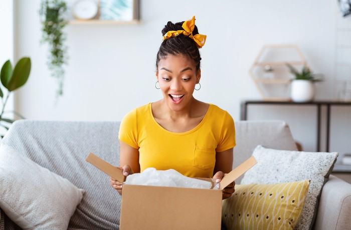 A woman excited as she opens up a box.