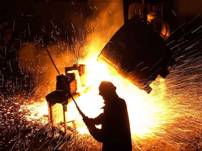 A man standing in front of hot sparking steel.