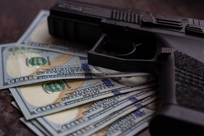 Handgun laying atop $100 bills