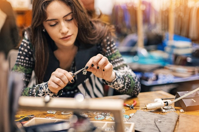 Young woman crafting jewelry in a workshop.