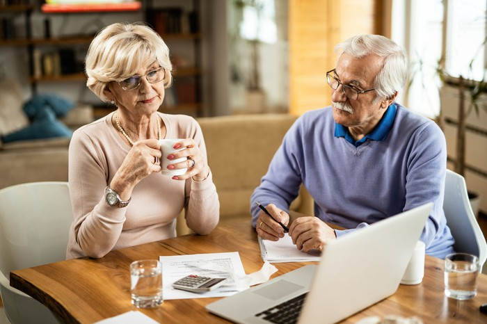 Older man and woman at table with notebook, documents, calculator, and laptop