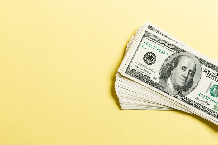 Stack of hundred dollar bills against a yellow background