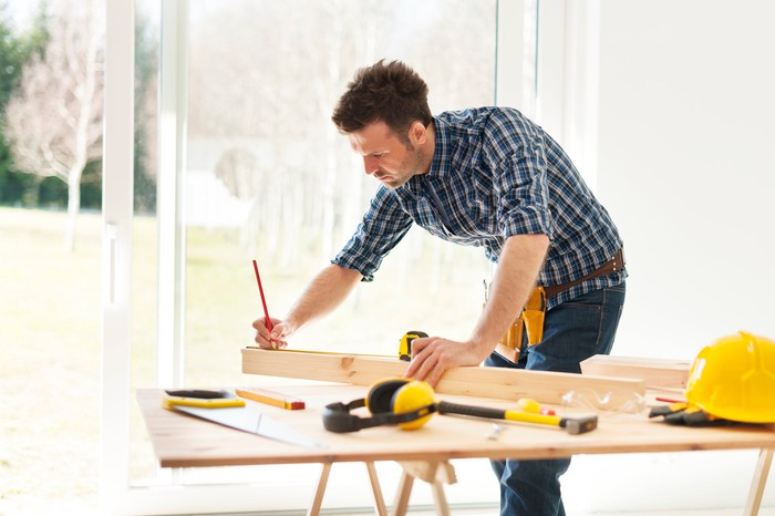 A man marks a measurement on a piece of wood on a work bench.