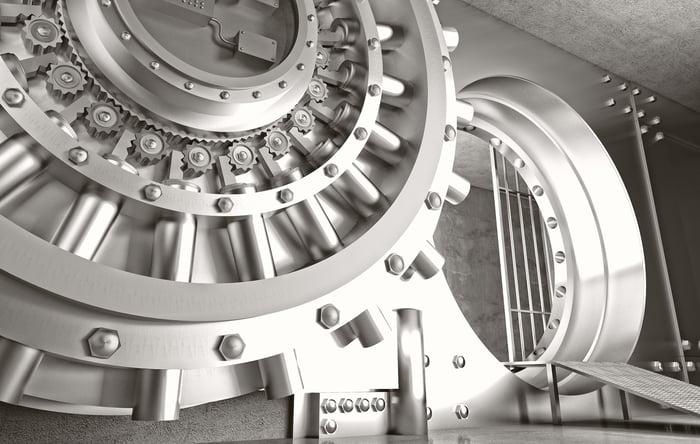 Grande voûte de banque en métal, avec porte ouverte et rampe menant au coffre-fort.