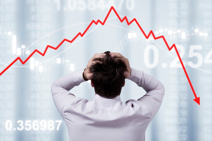 With his hands on his head, a businessman looks at a down-trending red arrow.
