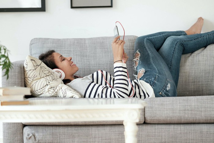A woman lying on the couch watching something on her phone