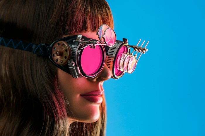 A woman wears a pair of futuristic steampunk glasses.