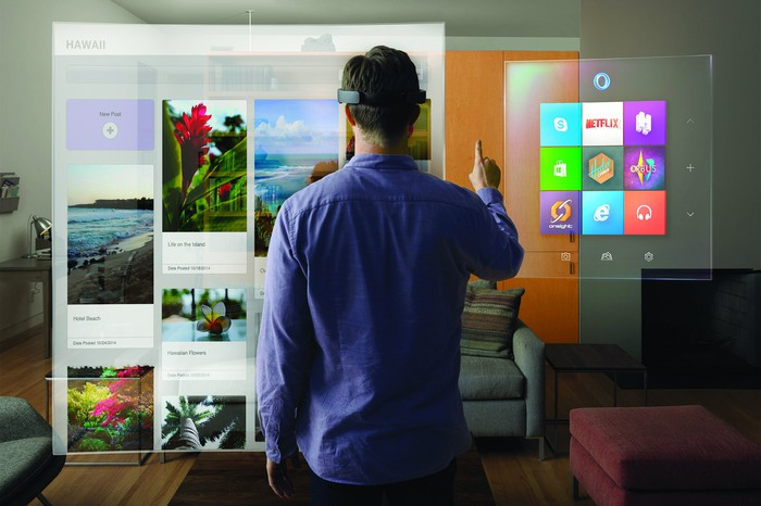 A man uses the HoloLens in his living room.
