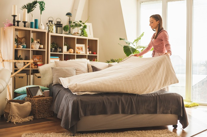 A woman making  a bed.