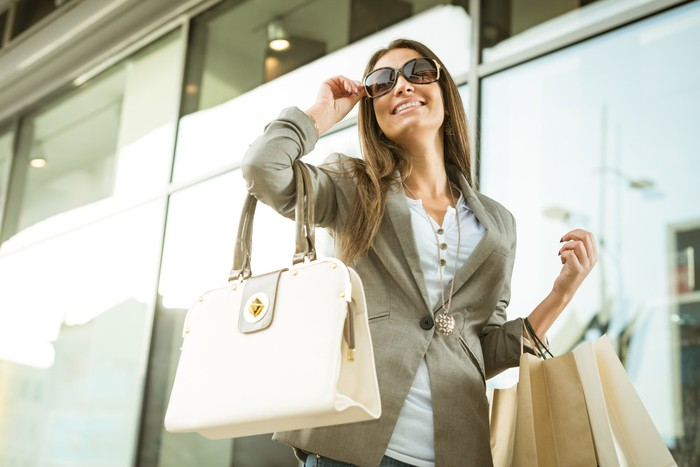 A woman with a luxury handbag and shopping bags.