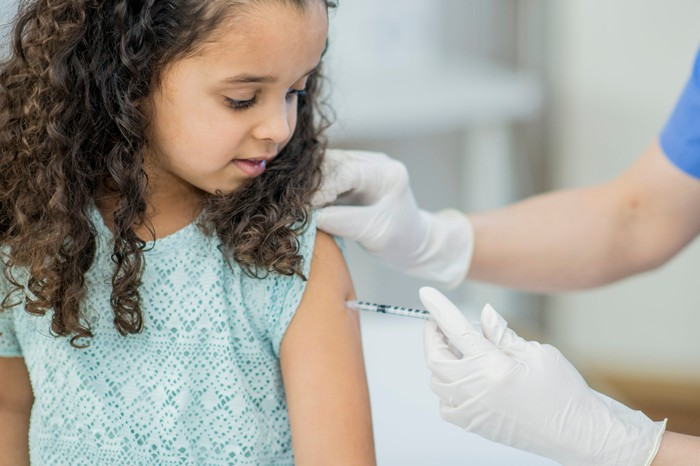 A gloved healthcare worker vaccinates a little girl.