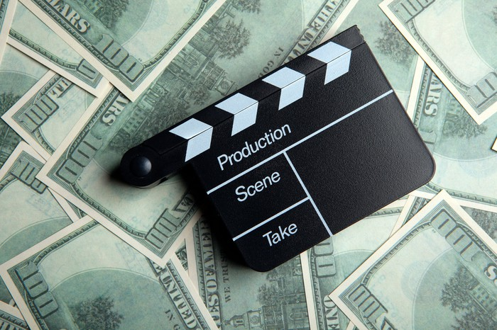 A movie director's clapper resting on a large pile of hundred-dollar bills.