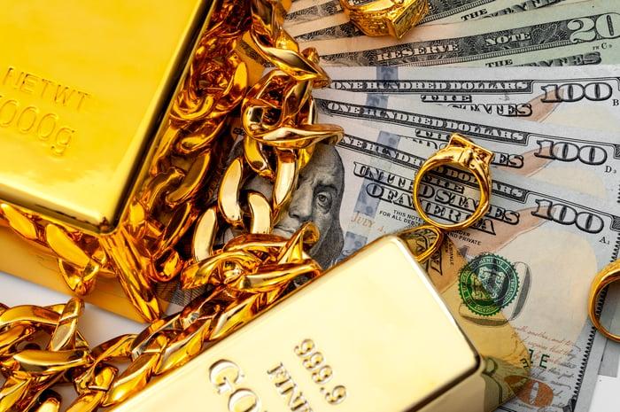 Lingots d'or et bijoux à côté des liquidités américaines.