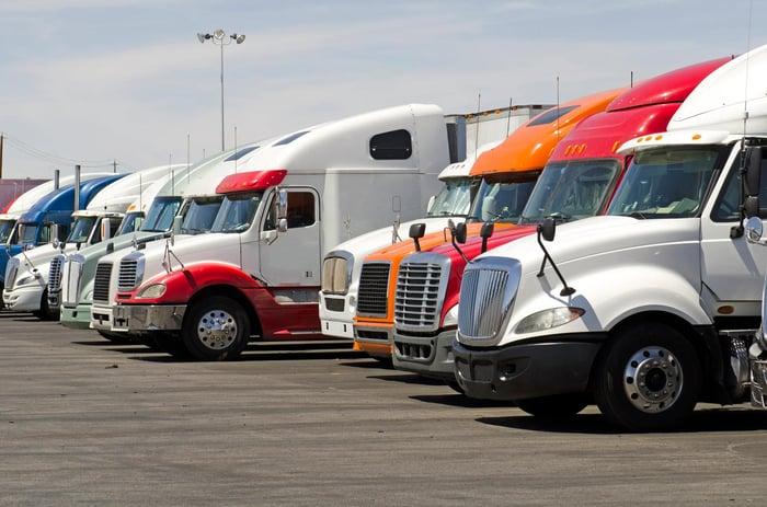 Longue rangée de camions semi-tracteurs de différentes couleurs dans un parking.