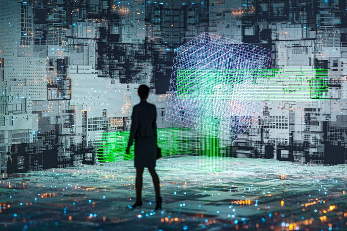 A person standing in a room with every surface covered in screens of data.