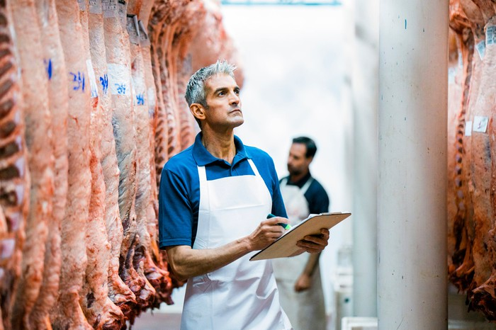 Inspectors in white aprons examine hanging sides of beef in a meatpacking plant.