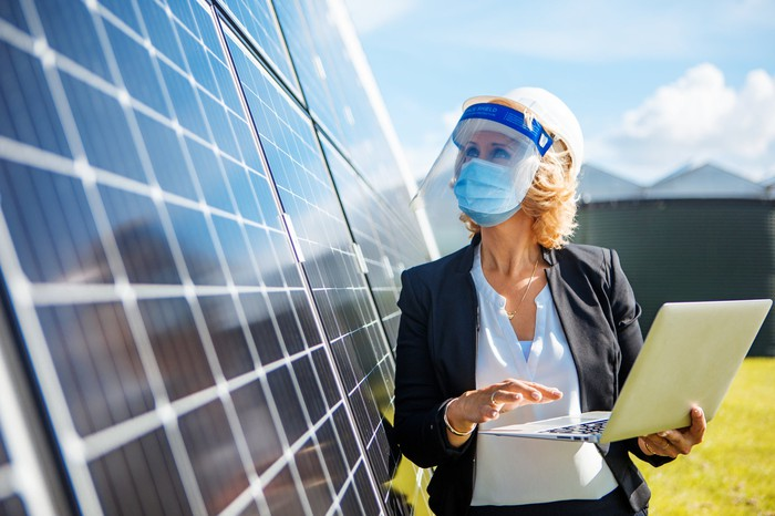 A woman holding a laptop and looking at solar panels.