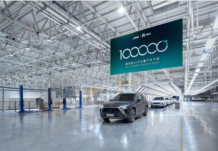 A NIO ES8 electric SUV rolls off the assembly line under a banner commemorating the occasion.