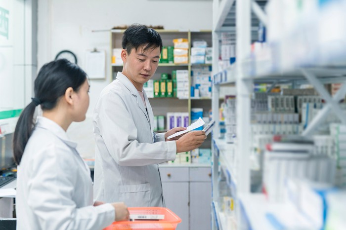 Two pharmacists look at shelves of medication.