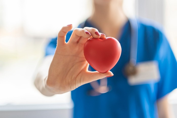 A doctor holds a heart symbol.
