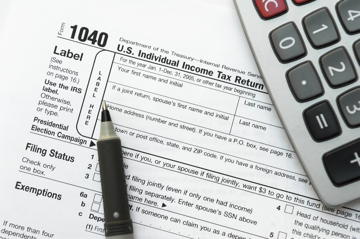 IRS form 1040 with a pen and calculator.