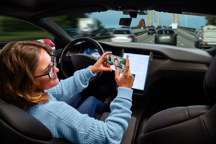 A woman on a phone riding in an autonomous car.