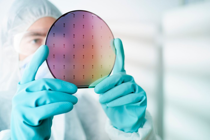 A worker examining a silicon wafer used to make computer chips.