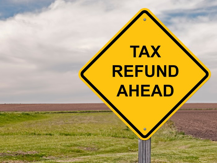 Diamond-shaped yellow sign outdoors that says tax refund ahead