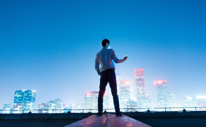 A young man looks at his phone before a night cityscape of a Chinese city.
