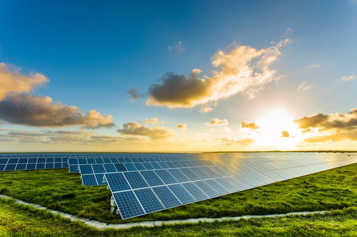The sun rises over rows of solar panels in a field.
