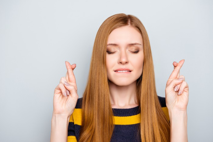 Woman with eyes closed and fingers crossed