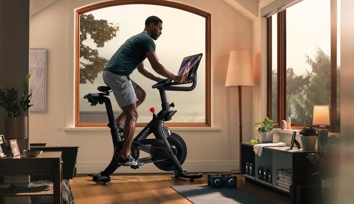 A man riding a Peloton Bike+ in his home.