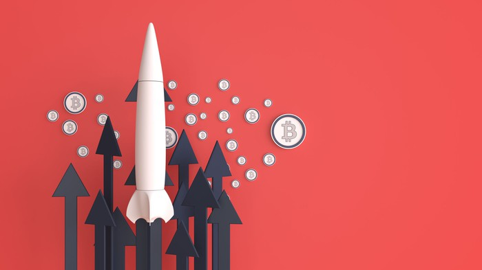 A rocket surrounded by Bitcoin logos.
