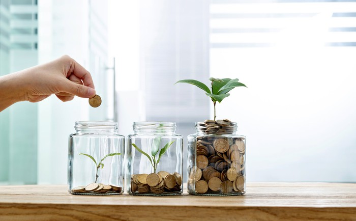 A hand places coins in three jars containing increasingly larger plants and piles of coins.