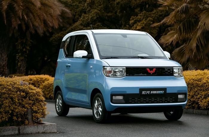 A blue Hong Guang Mini EV, a tiny electric commuter car.