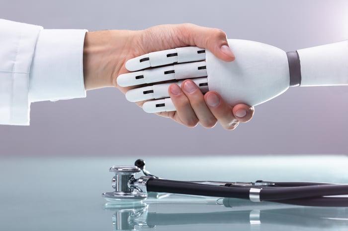 Une main humaine serre la main d'une main de robot.