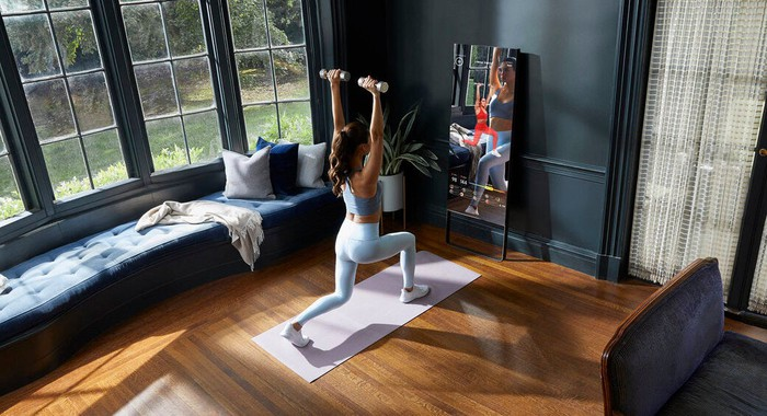 A woman lunges during a workout in front of a Mirror fitness device