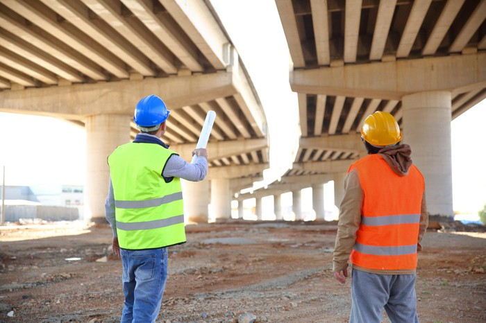 two construction workers look at the underside of a bridge under construction