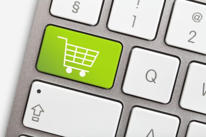 A light green shopping cart button on a modern computer keyboard.
