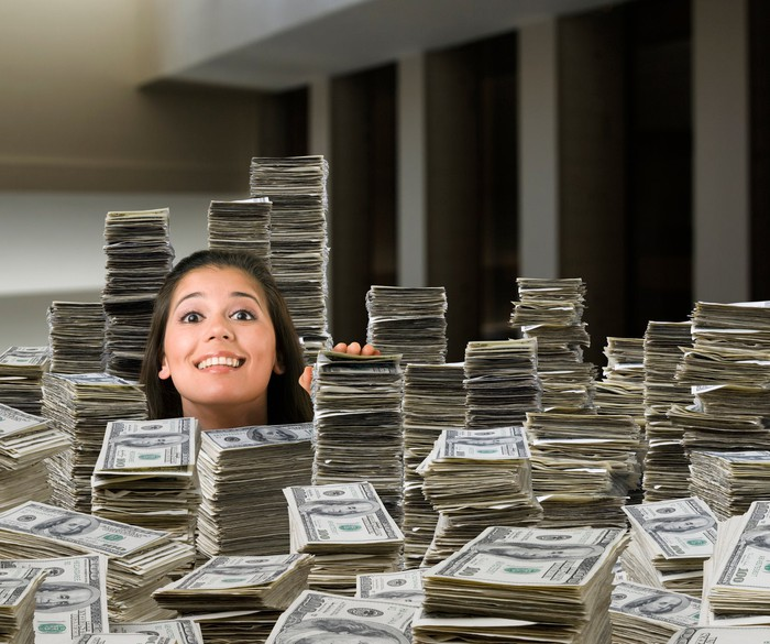 A woman's head pops out of stacks of dollar bills filling an office.