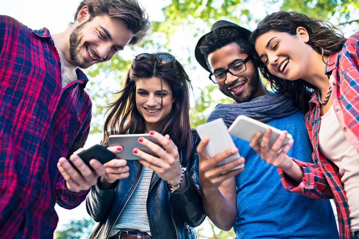Quatre jeunes adultes souriant et regardant leurs téléphones