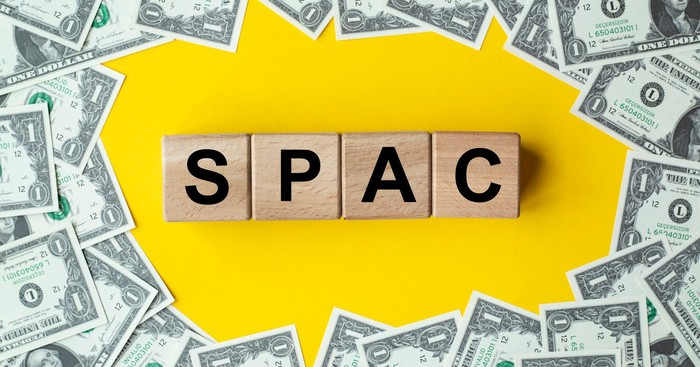 Letter tiles spelling SPAC surrounded by $1 bills.