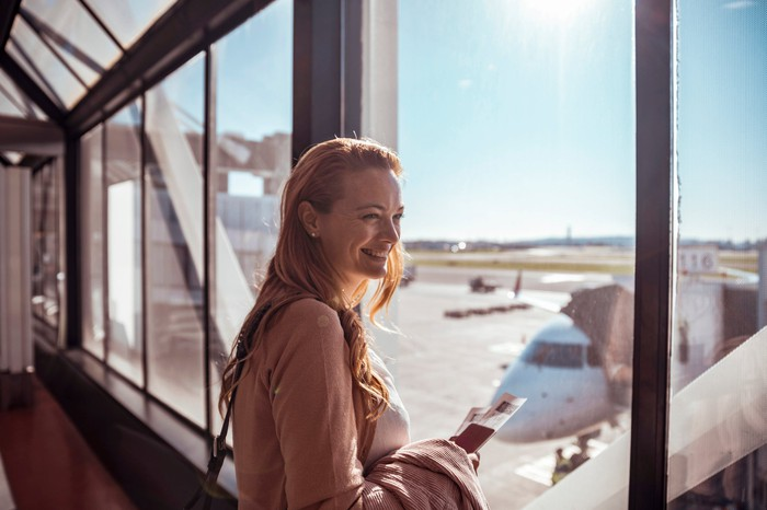 A woman looks out the window at an airport.