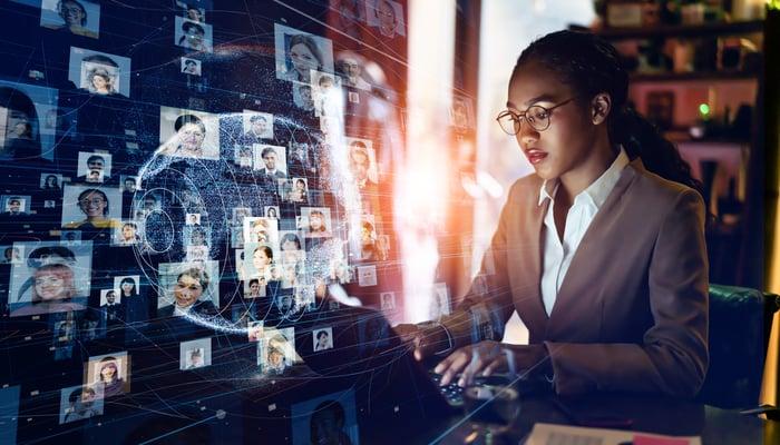 Une femme devant un ordinateur avec une matrice de réalité virtuelle de profils de médias sociaux devant elle